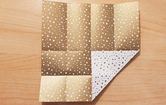 Origamipapier wird von der Ecke unten rechts in die Mitte gefaltet