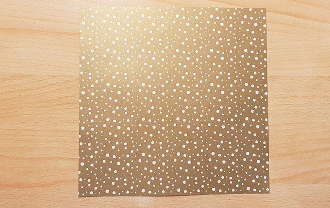 Quadratisches Origamipapier mit goldener Seite nach oben