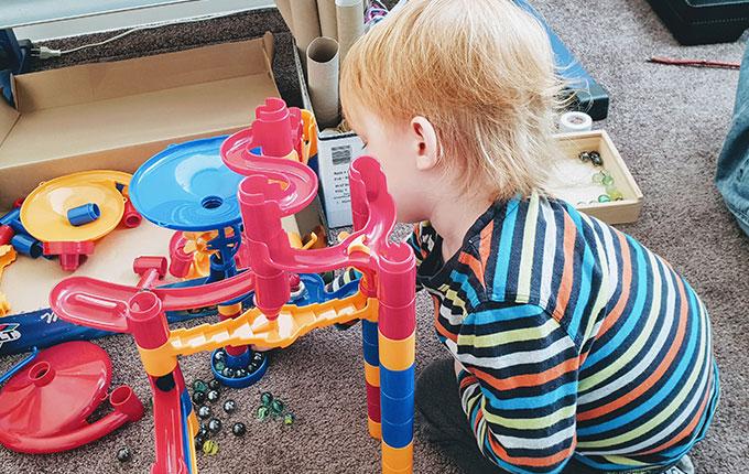 Kind baut Murmelbahn auf