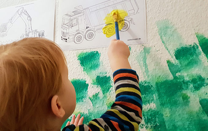 Kind bemalt Kipplaster mit gelber Acrylfarbe