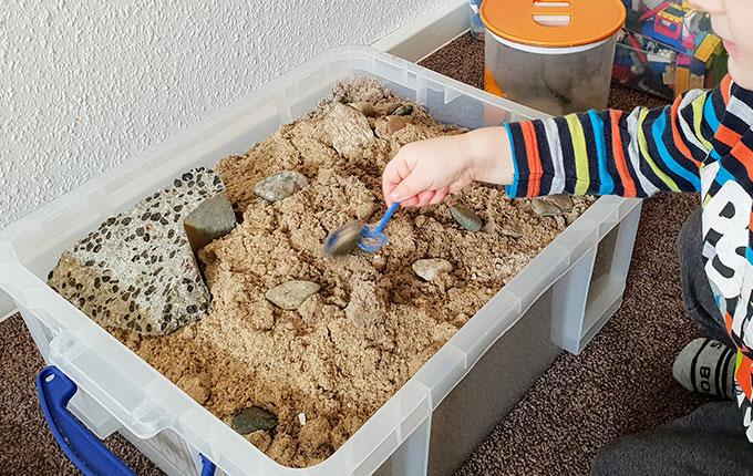 Kind buddelt mit kleiner Schaufel in Kiste voller Sand