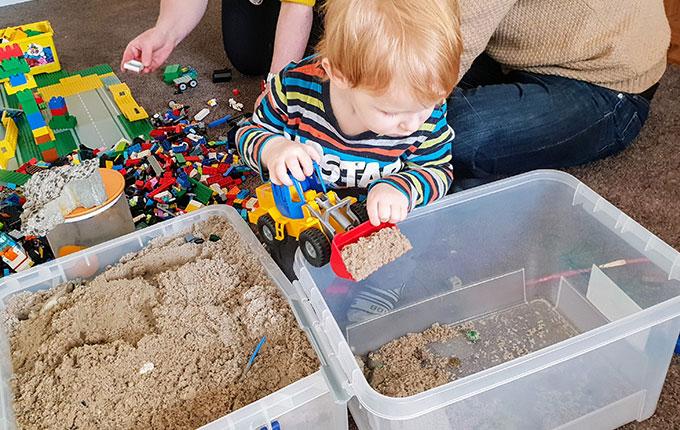 Kind buddelt mit Radlader Sand aus Sandkiste