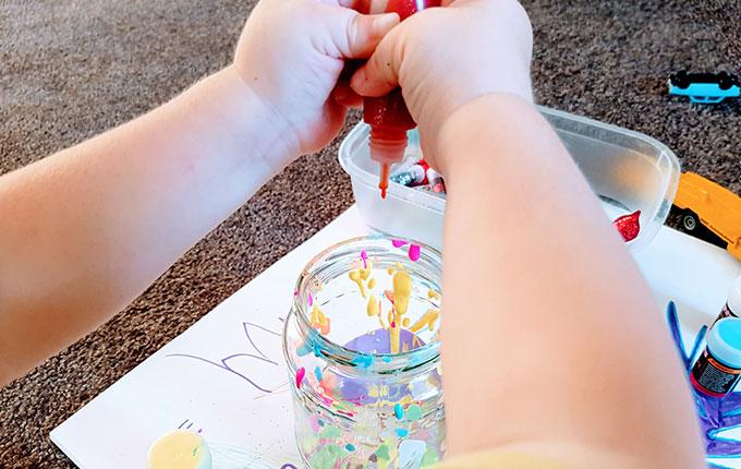 Kind drückt Farbe aus Farbtube in ein Glas