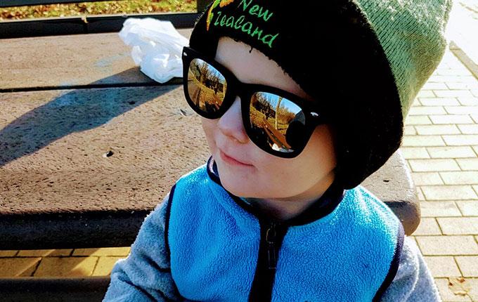 Kind mit dicker Mütze und Sonnenbrille