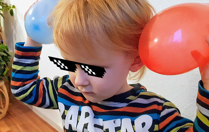 Kind reibt sich Luftballons am Kopf