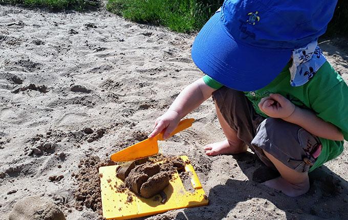 Kind schneidet mit Plastikmesser durch Sandform