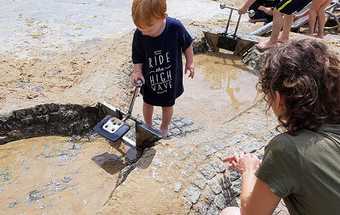 Kind spielt auf Wasserspielplatz