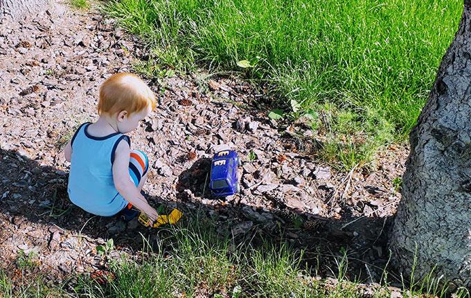 Kind spielt im Schatten eines Baumes
