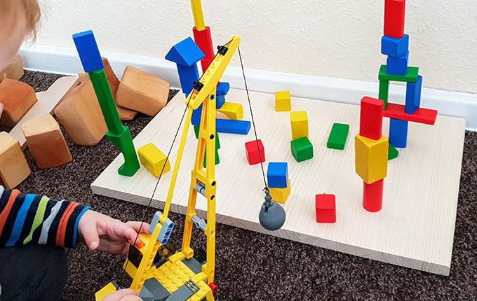 Kind stürzt Bausteine mit Abrissbirne ein