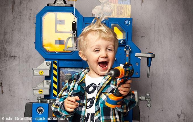 Kleiner Junge vor Werkbank freut sich über Bohrer