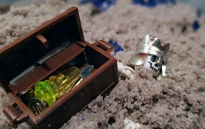 Lego Skelett mit goldener Krone und Schatzkiste im Sand vergraben
