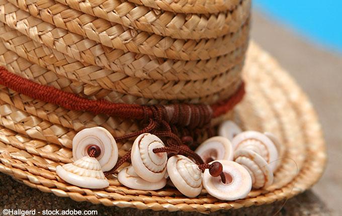 Strohhut mit rotem Band und Muscheln im Sand