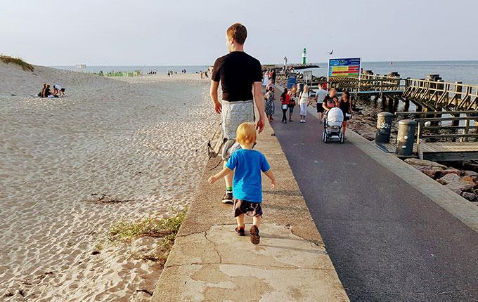Vater und Kind balancieren auf Mauer an der Ostsee
