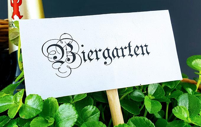 Biergartenschild im Korb umgeben von Pflanzen und Bier