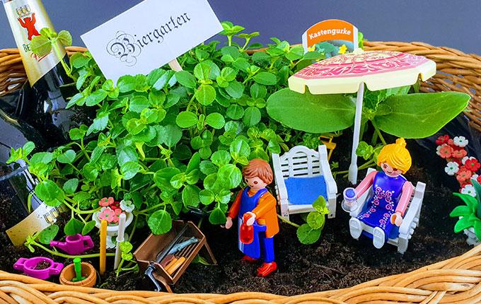 Geschenkkorb dekoriert mit Pflanzen, Bier und Playmobil als Biergarten