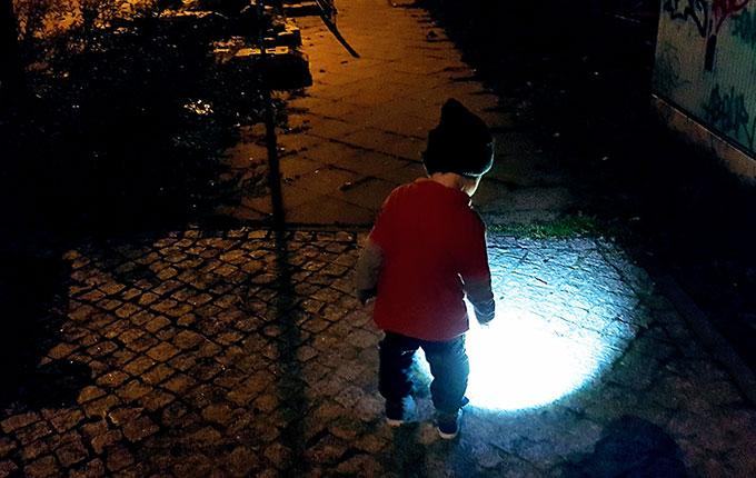 Kind leuchtet bei Nachtwanderung mit Taschenlampe auf den Boden