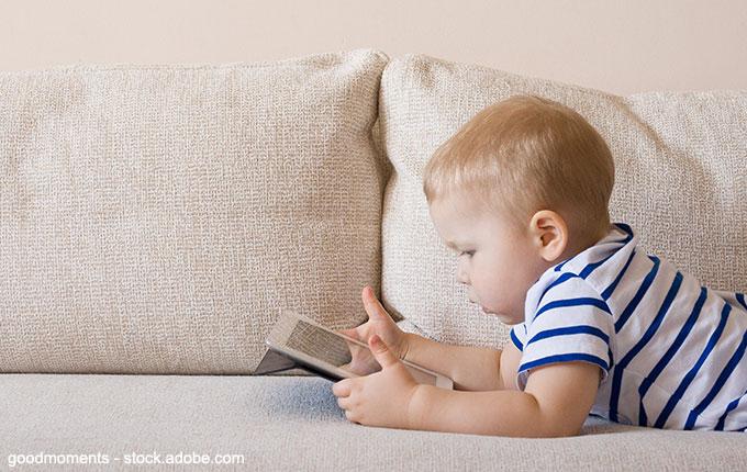 Kleinkind spielt liegend Tablet auf der Couch