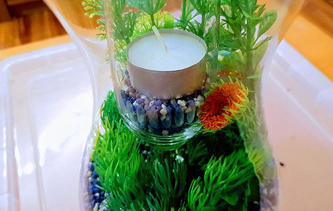 Sektglas mit Teelicht in einer Glasvase mit Aquariumkies und künstlichen Wasserpflanzen