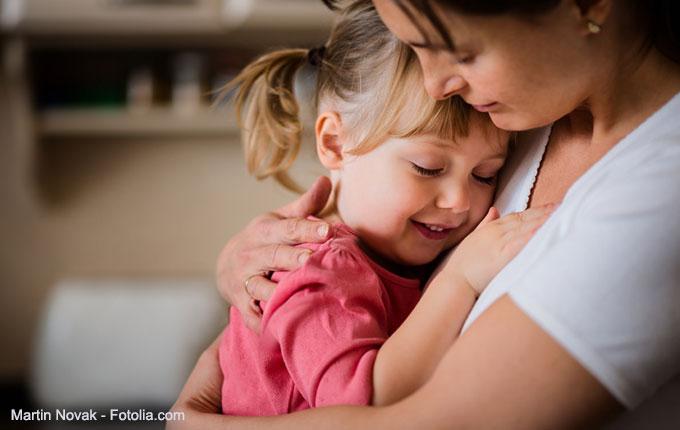 Kind lächelt in den Armen seiner Mama