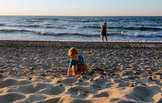 Kind sammelt Schätze am Strand