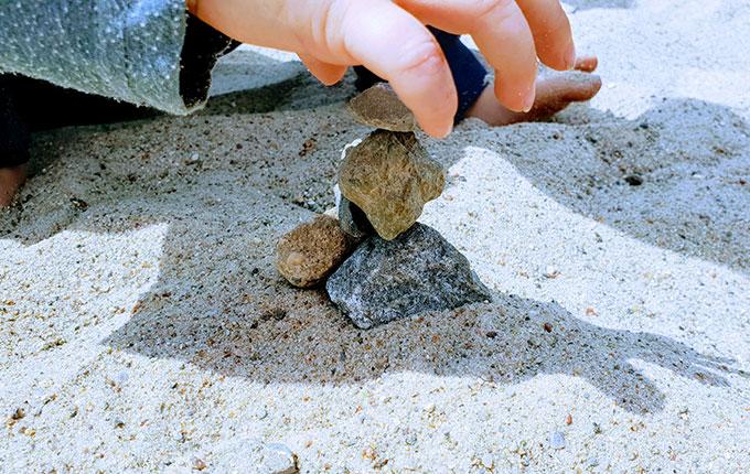Kind stapelt kleine Steine übereinander