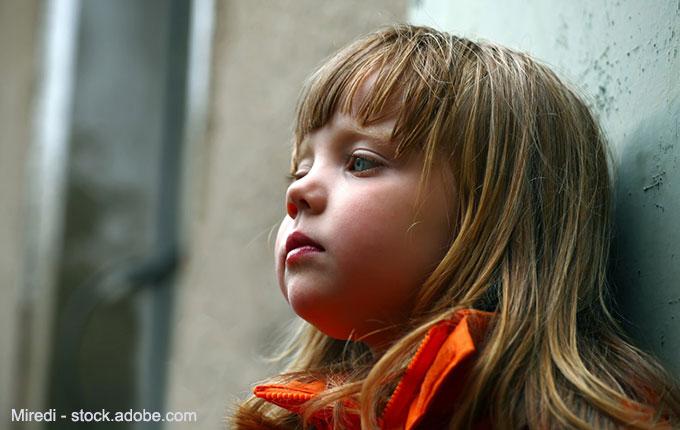 Trauriges Kind lehnt an einer Wand