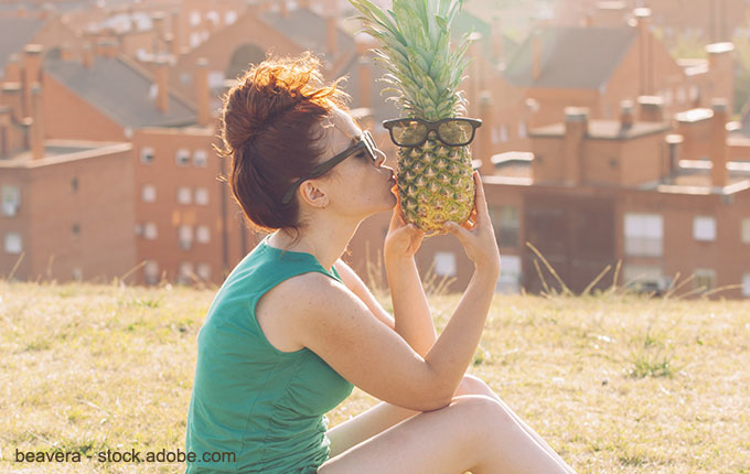 Frau küsst Ananas mit Brille