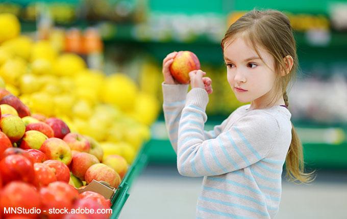 Kind klopft an Apfel im Supermarkt
