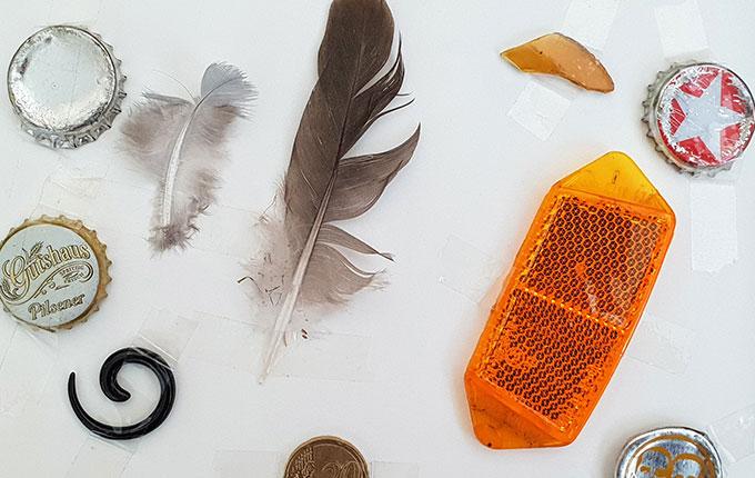 Sammelbuch Seite mit Federn, Kronkorken, Glasscherben, Reflektor, Münze und Ohrring