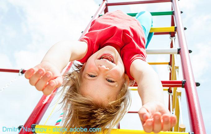 Kind baumelt an Klettergerüst und hat Spaß