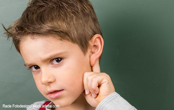 Kind hält sich Finger ans Ohr und schaut kritisch