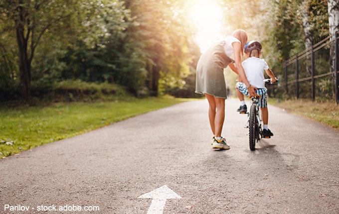 Mutter hilft Kind beim Fahrradfahren