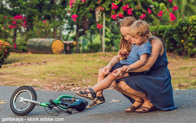 Mutter klebt Pflaster auf Knie vom Kind, das mit dem Laufrad hingefallen ist