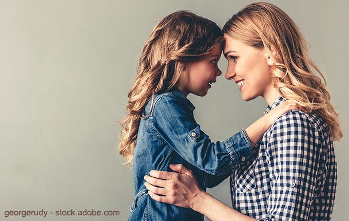 Mutter und Tochter Stirn an Stirn lächeln sich an