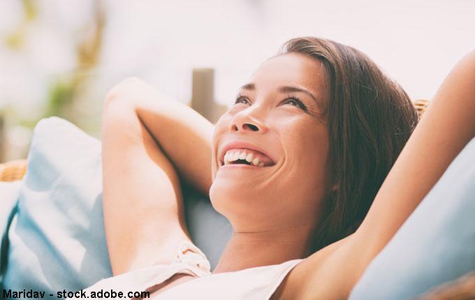 Frau lehnt sich zurück und lacht
