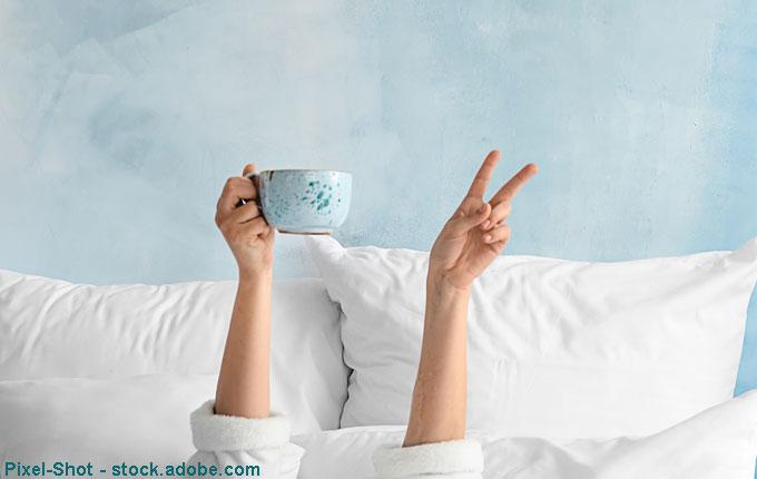 Frau liegt im Bett und hält Tasse in der Hand und zeigt Peace Zeichen.jpg