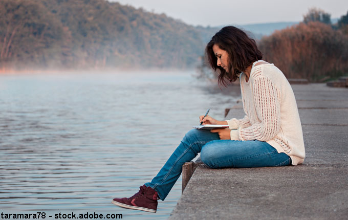 Frau schreibt am Steg