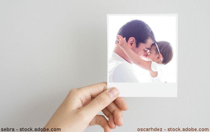 Hand hält Foto von Papa und Kind fest