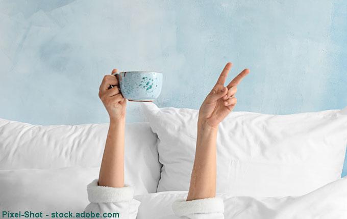 Hand hält Tasse im Bett hoch