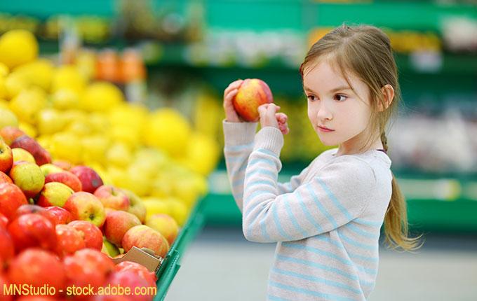 Kind prüft Apfel im Supermarkt kritisch