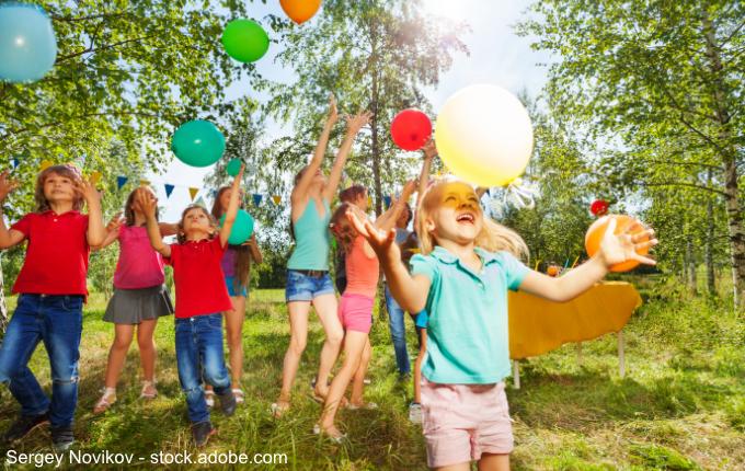 Kinder spielen mit Luftballons im Grünen