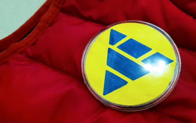 Button mit blauem Beyblade Symbol auf gelbem Hintergrund