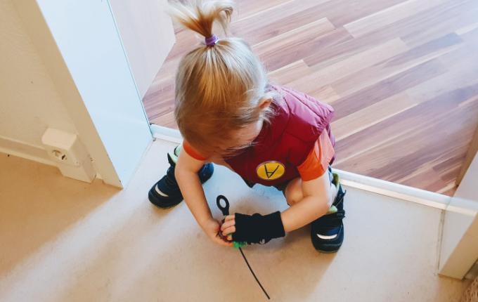 Kind im Beyblade Kostüm spielt Beyblade