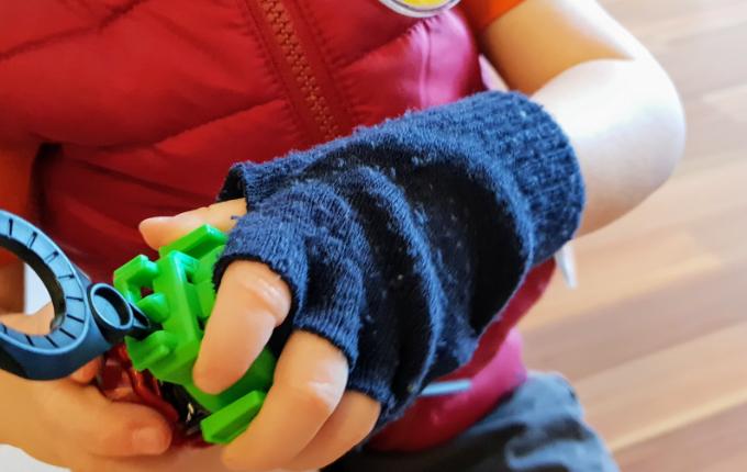 Kind im Beyblade Kostüm und blauen Halbfinger Handschuh spielt Beyblade