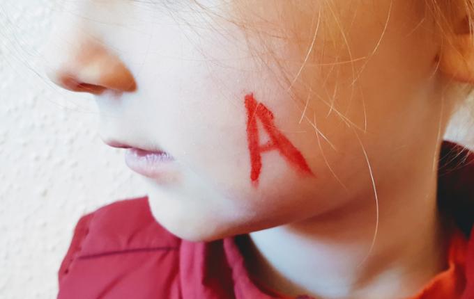 Kind mit geschminktem rotem A auf der linken Wange