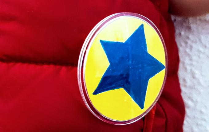 selbst gemachter Button mit blauem Stern auf gelbem Hintergrund