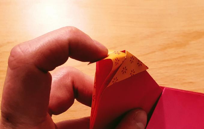 Finger faltet Kopf von Origami Huhn mit Kopftuch
