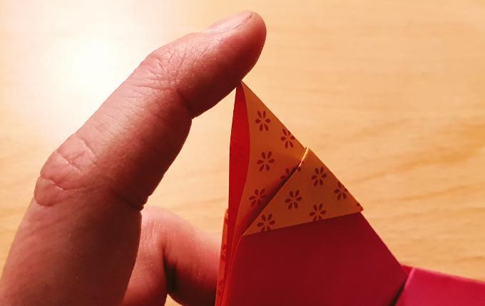 Finger knickt Spitze von Origami Huhn