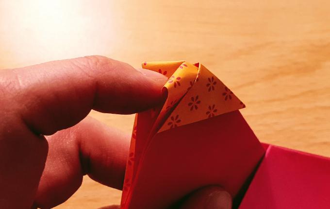 Finger knickt Spitze von Origami Huhn nach innen