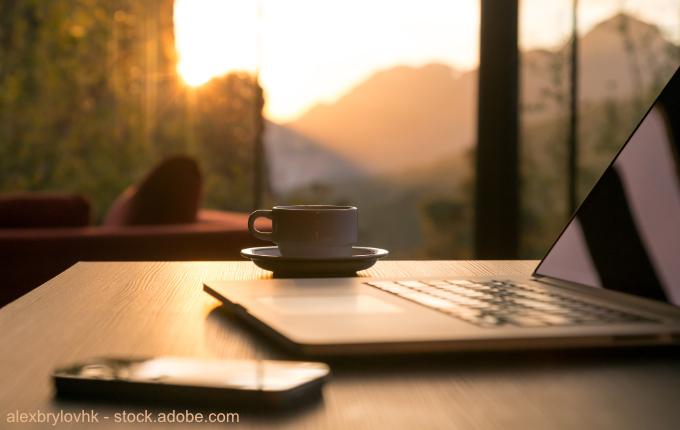 gemütlicher Arbeitsplatz mit Laptop, Telefon, Tasse und schönem Ausblick